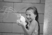 a little girl squirting a water gun