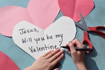 A little girl drawing a Valentine's day card for Jesus