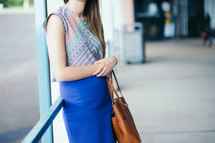 a woman with a purse waiting at a bus stop