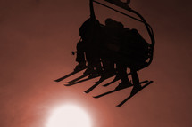 silhouette of skiers on a ski lift