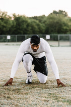 man with a runners stance on a grass sports field