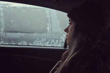 a woman looking out an icy car window