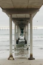 ocean under a concrete pier