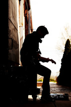Young, male guitar player sitting on amp in an industrial alley with electric guitar with pedal board. Photo is taken outside and the guitar player is silhouetted against white.