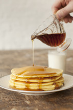 Pouring syrup over a stack of pancakes.