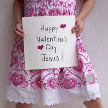 A little girl holding up a sign that reads Happy Valentine's day Jesus