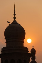 Bird flying over Islamic Mosque at sunset.