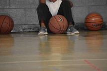 An African American boy waiting on the sidelines to join a basketball game