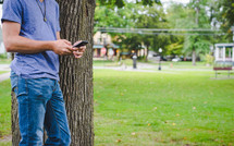 man texting beside of a tree
