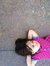 a child lying on pavement