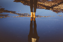 woman in boots standing in a puddle