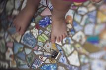 toddler feet on mosaic tiles