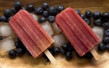 Frozen Homeamde Blueberry Popsicles in a Wooden Bowl