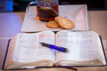 pen on an open Bible and tea with cookies