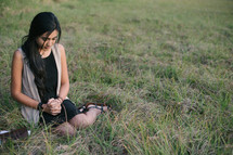 young woman praying in grass