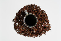 Coffee mug in the middle of coffee beans