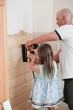 father and daughter using a nail gun to put up shiplap
