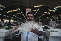 man holding a fish in a seafood market