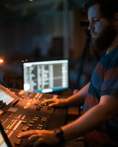 A sound technician working a sound board.
