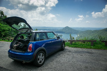 A small blue car parked at an overlook and facing mountains and a lake.
