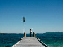 a woman standing on a dock looking out over the water
