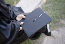 a graduate holding her graduation cap