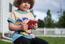 toddler girl holding a cellphone
