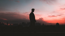 silhouette of a man standing outdoors in front of a city at sunset