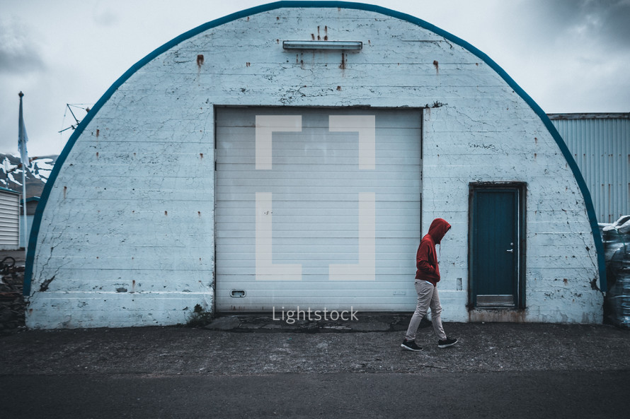 a man walking in front of a storage building