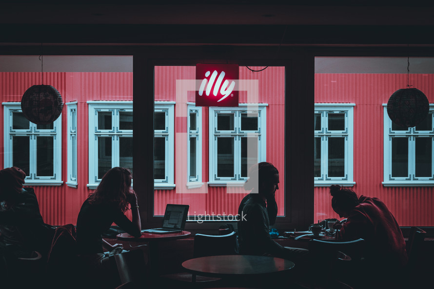 people sitting in window seats in a cafe