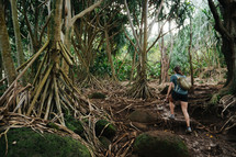 a woman hiking through a forest