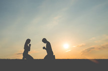 silhouettes of a couple kneeling in prayer together