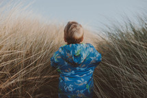 a toddler in a coat walking through tall grasses