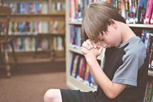boy child praying in a library