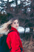 teen girl outdoors in a red coat and book bag