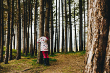 a girl in a raincoat hugging a tree
