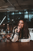 a shy young woman sitting in a coffee shop