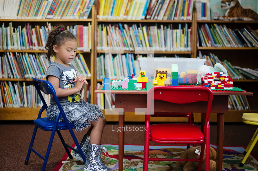 girl child praying and a table of lego building blocks