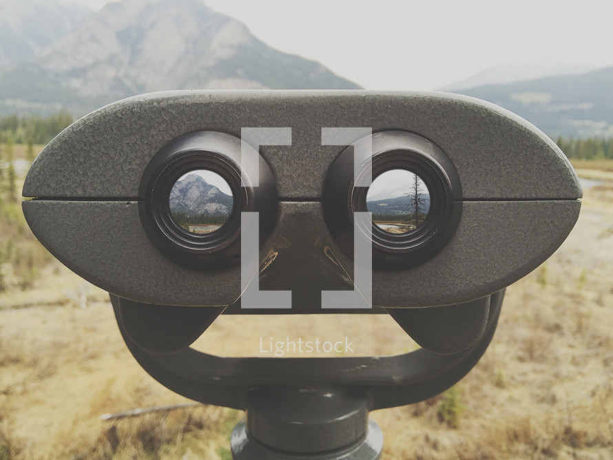 an iPhone capture of look out binoculars in a remote mountain area - with added photos in vision holes