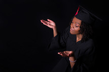 an African American woman graduate with raised hands
