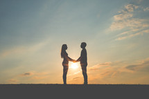 a couple in love holding hands at sunset