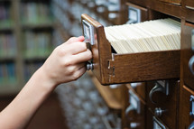 Library card catalog cabinet with a hand opening drawer.
