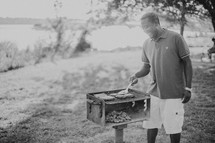 A man cooking hamburgers and hot dogs on an outdoor barbecue grill.