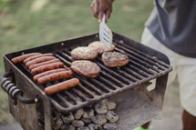 A man cooking hamburgers and hot dogs over coals on an outdoor barbecue grill.