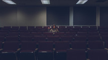 a woman sitting in an empty auditorium