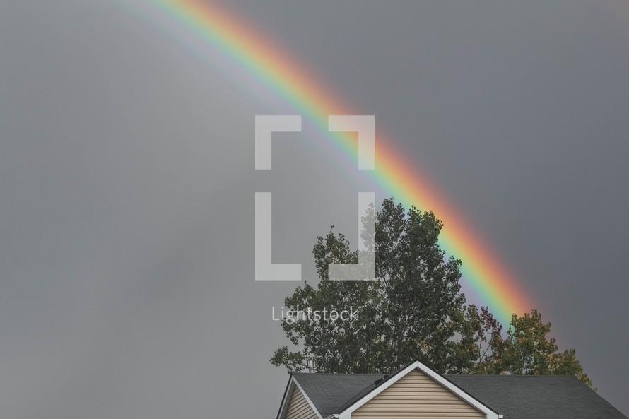 rainbow over a house roof