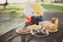 hamburgers and hotdogs on a table outdoors with a beach ball