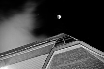 looking up at a full moon above a building