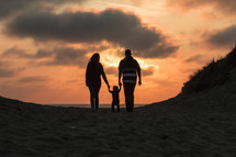 silhouette of a family on a beach at sunset in fall
