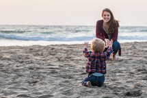 a toddler boy and mother on a beach